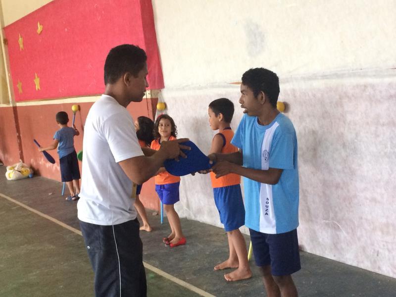 Professor de Educação Física e Coordenador do Projeto Mini Tênis Inclusivo, Itair Medeiros,  auxilia o estudante Marcelo Castro.   Foto: Natasha Albarado.