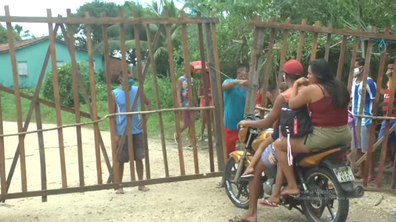 Um portão de madeira, construido na entrada da comunidade, limita o acesso ao local.