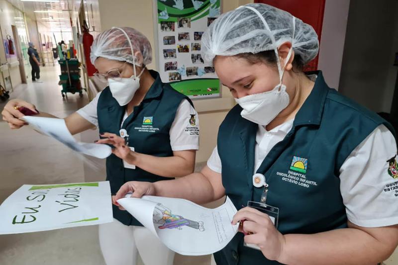 Enfermeiras lendo suas cartinhas escritas pelos pacientes.