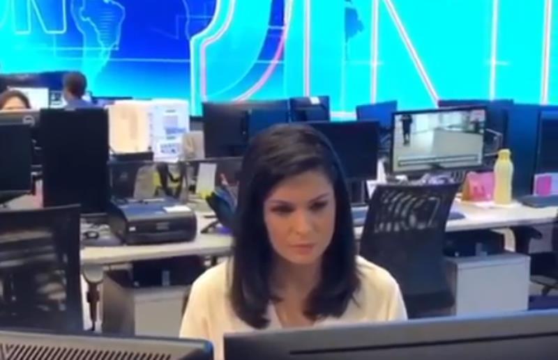Priscilla na redação do Jornal Nacional e o telão característico do telejornal, ao fundo