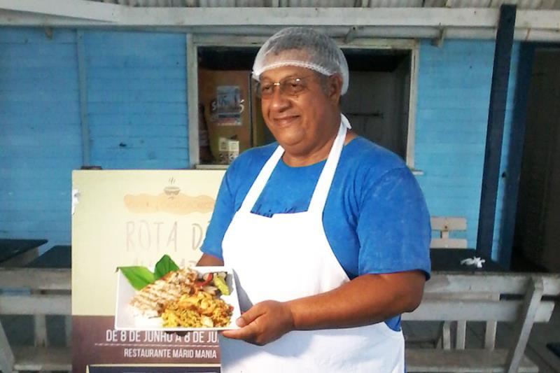 """Senhor Mário, proprietário da barraca Mário Mania, com o prato """"Avuado Pescado""""."""