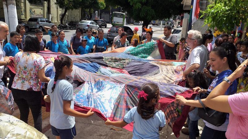 No final do evento, com um tecido levado ao centro, no chão, foi formada uma mandala com as crianças em volta, simbolizando a inclusão