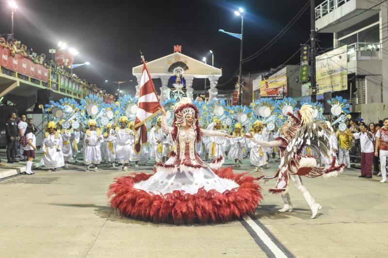 O casal de mestre-sala e porta-bandeira do Quem São Eles trouxe as cores tradicionais da escola, o branco e o grená