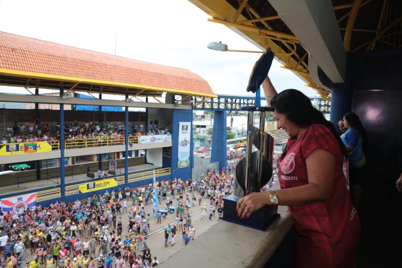 A presidente da Boêmios da Vila Famosa, Michelle Araújo, levanta o trófeu de campeã do terceiro grupo de comemora o acesso para o segundo grupo