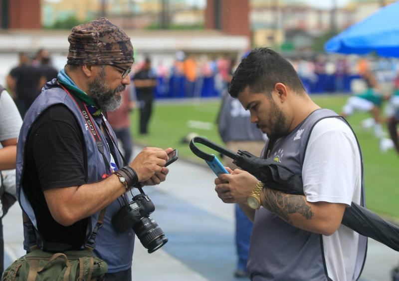 Osmarino Souza e Bruno Cruz trocando joguinhos de celular. Detalhe para o guarda-chuva do Bruno.