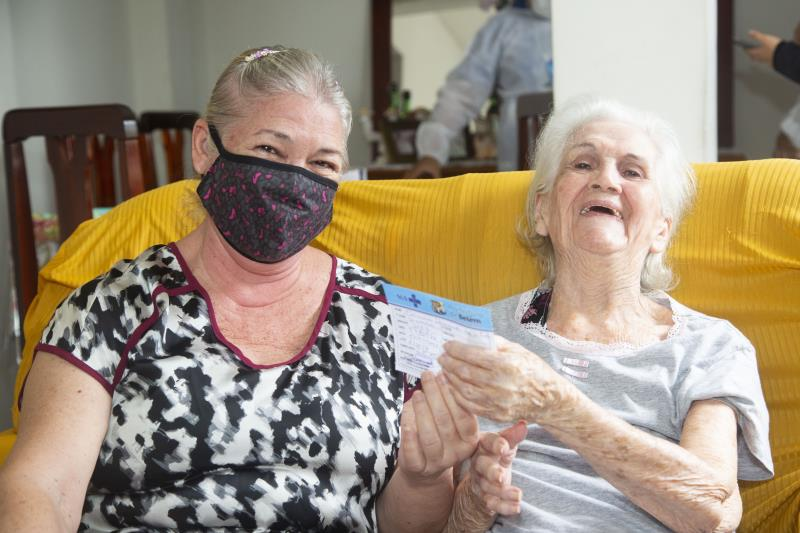 Depois de imunizada Carmem Silva, ao lado da filha Célia Maria, sorria aliviada.