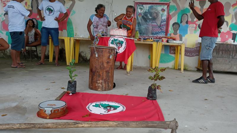 O bolo de 22 anos foi cortado pelas mulheres do assentamento. A bandeira, plantas, enxada e o tambor são simbologias do MST.