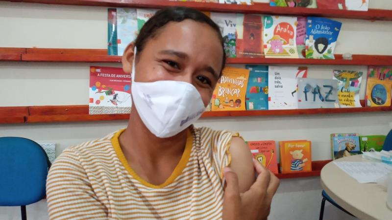 """A alegria da Carla Beatriz após ser imunizada com a primeira dose da Pfizer. """"Me preparando pra voltar às aulas com saúde""""."""