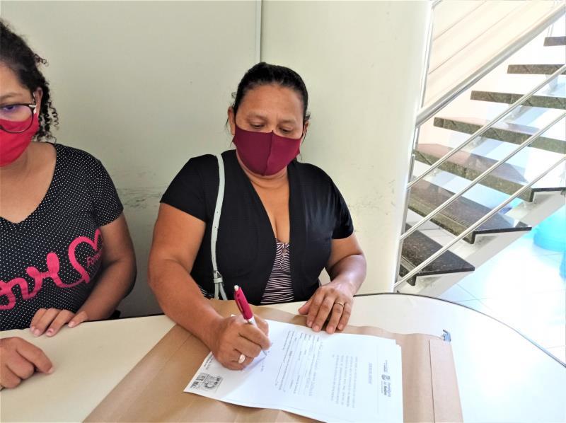 A moradora Alda Campelo, remanejada do Canal da Quintino, assina o Termo de Adesão.